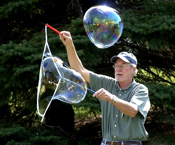 Person making really big bubbles with two wands.