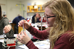 Close up of a student working with a test tube in a chemistry class.