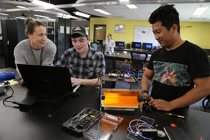 Two students working on their robot with instructor present.