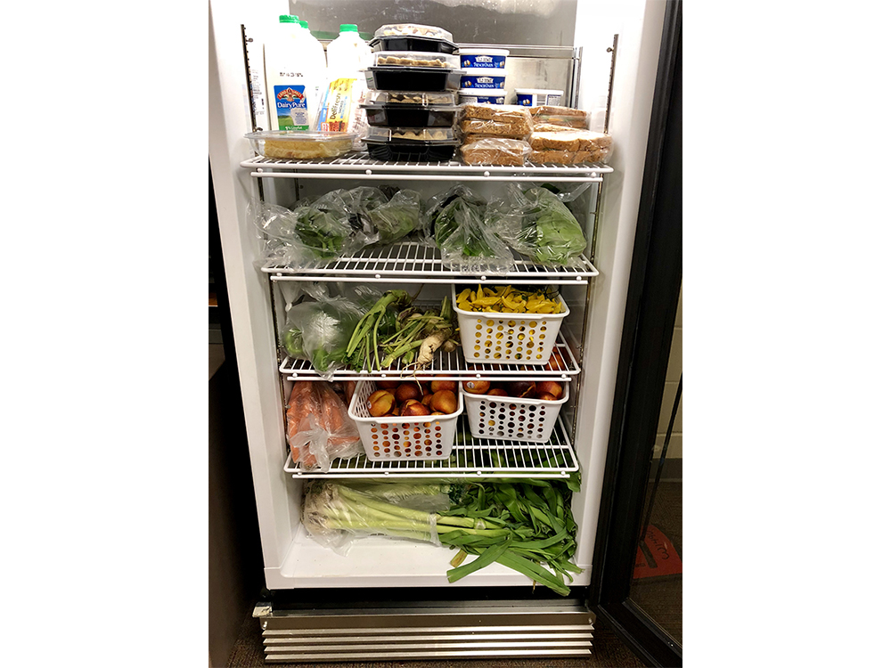 Refrigerator filled with fruits, vegetables, and sandwiches.