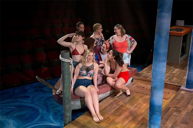 Actors sitting in a boat in the play Last Summer at Bluefish Cove