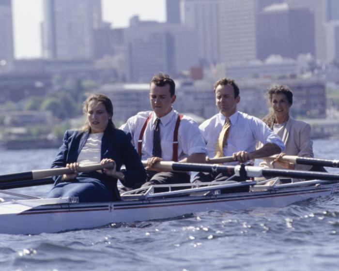 business team rowing in a boat