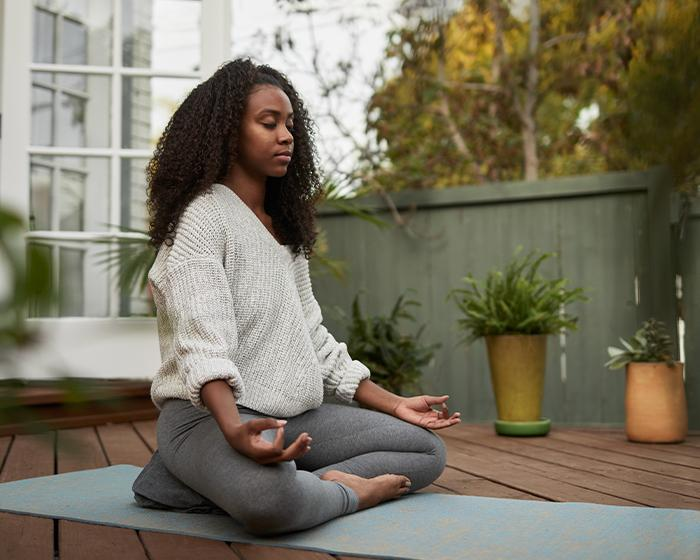 Student meditating in peace outside on the back patio at home.