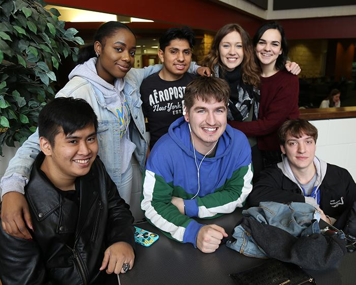 Group of students standing at a table on West Campus.