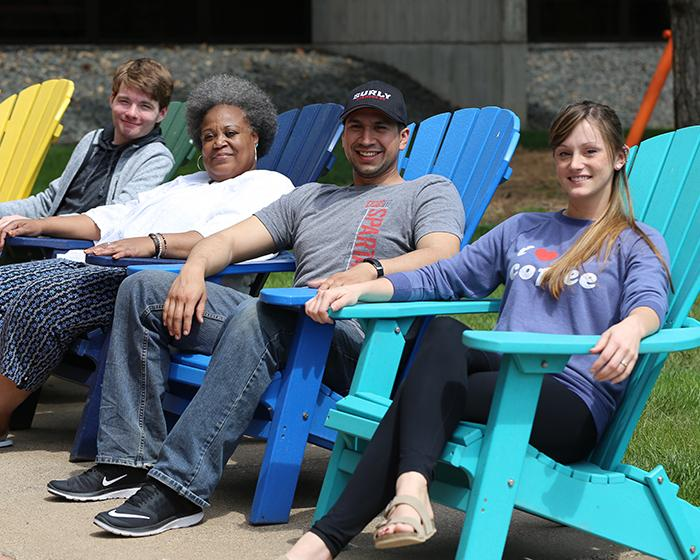 Group of students outdoors sitting on brightly colored chairs.