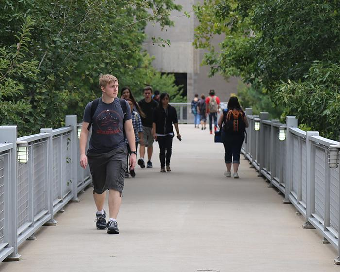 Students walking across the bridge during the summer.