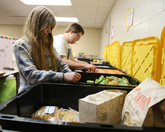 Two students organizing food in the Resource Support Center on campus.