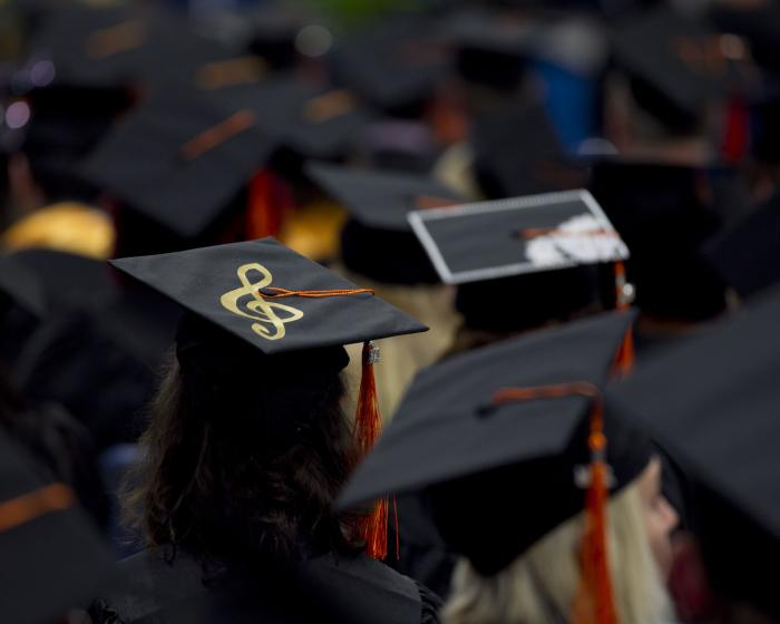 Image of graduates standing in crowd and a close up of a girl's graduation cap with a treble clef on it.