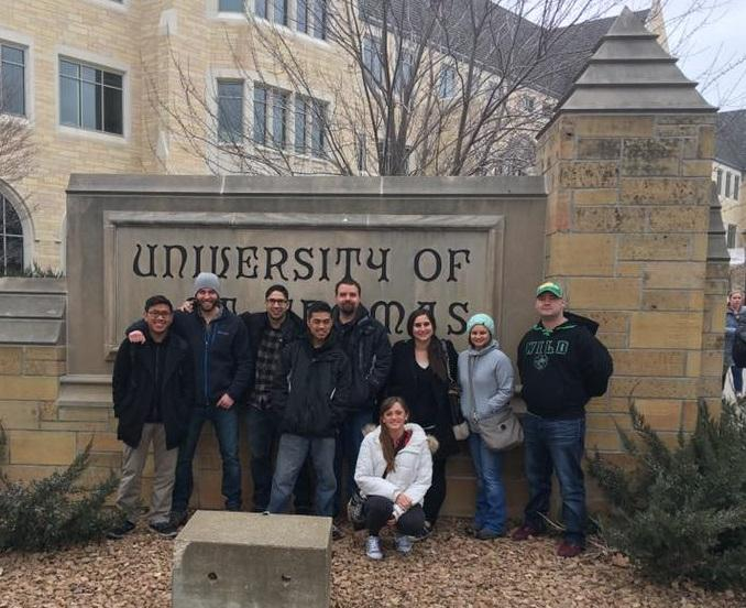 Image of veterans standing in front of university sign.