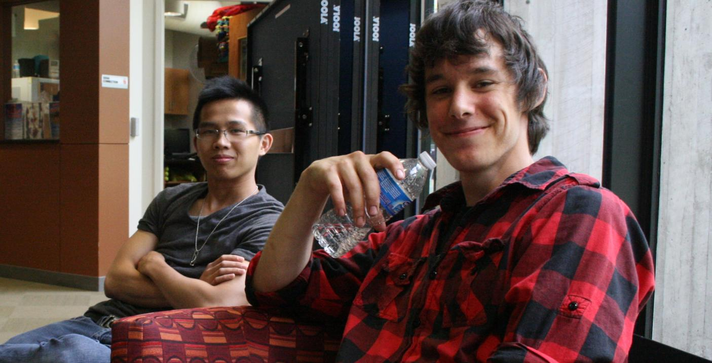 Image of two students sitting in front of windows.