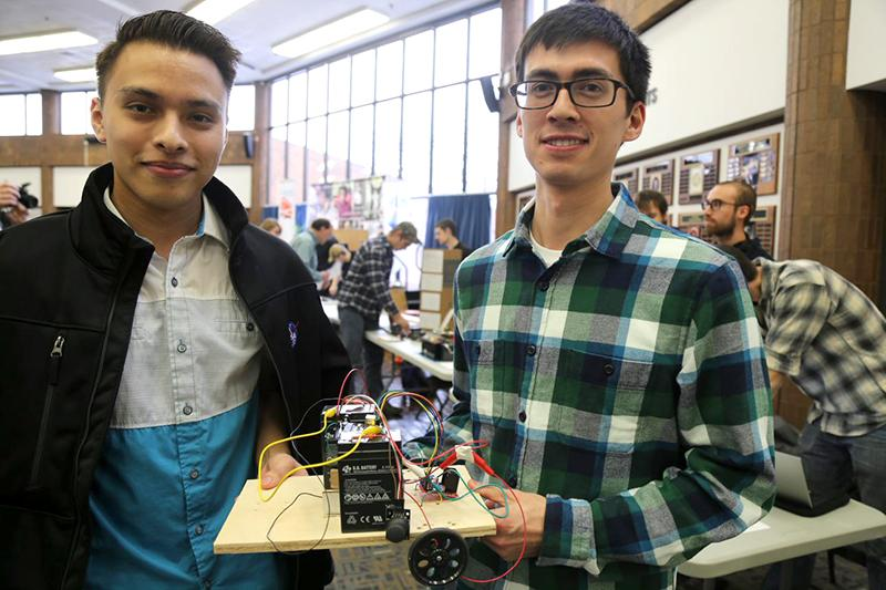 Students holding a robot with more student-made robots in the background.