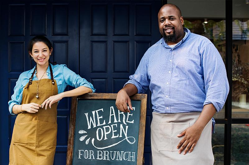 Two business owners standing in front of an open sign
