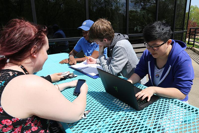 Students studying outdoors at a bright blue picnic table.