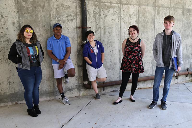 Group of students outdoors in front of a cement wall.