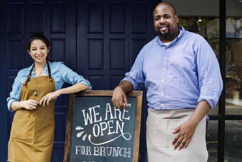 Business owners standing in front of their restaurant with a sign advertising brunch.