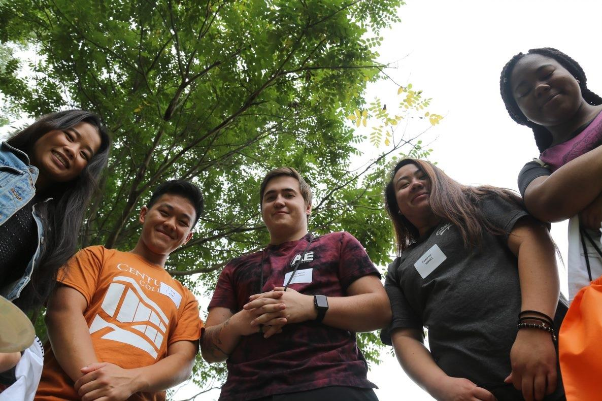 Image of five students outside looking down at the camera.