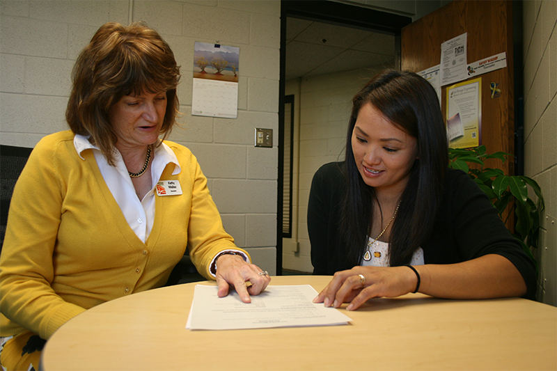 Advisor talking with a student while she points at a piece of paper.