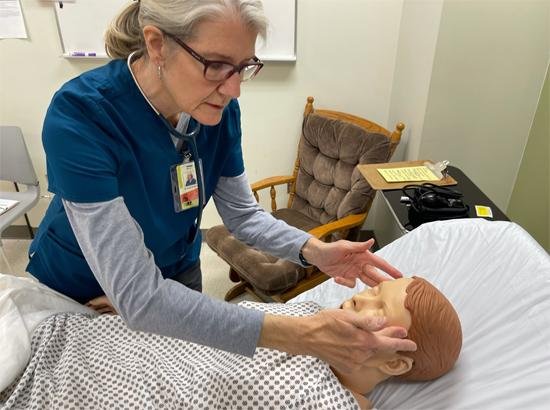 Student practicing a wellness check on a mannequin patient.