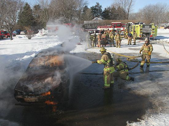 Firefighting students wearing uniforms outdoors spraying a car that is on fire with a hose.