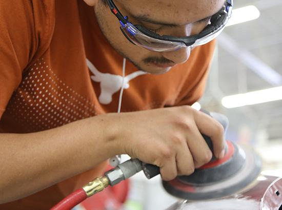 Student sanding the exterior of a vehicle.