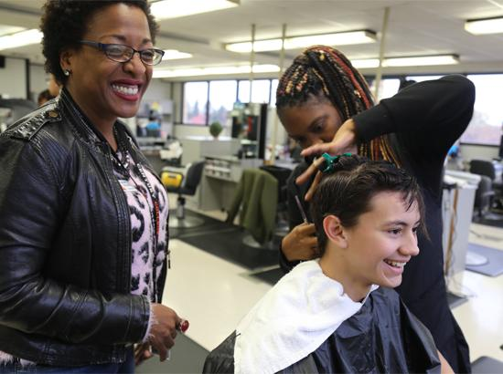 Cosmetology student and teacher cutting customer's hair.