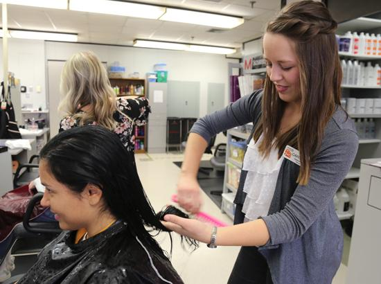 Cosmetology student combing customer's hair.