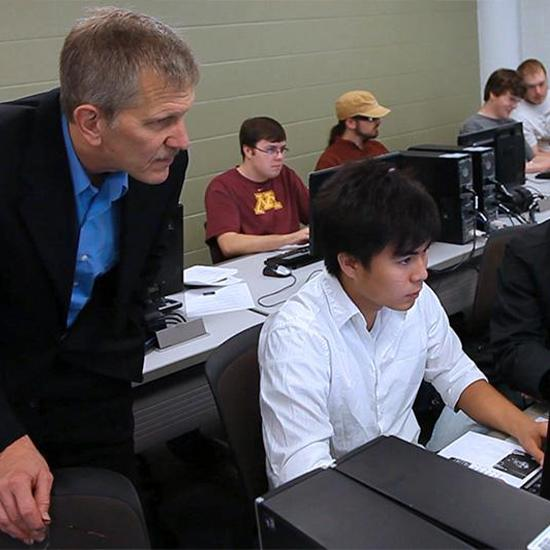 Faculty working with students in a computer lab.