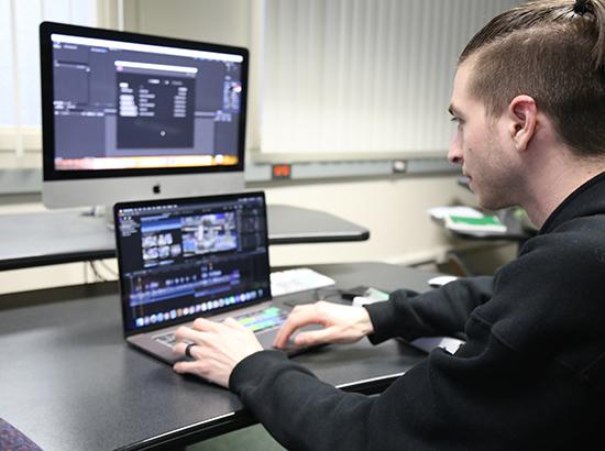 Student editing a film on an Apple laptop and monitor.