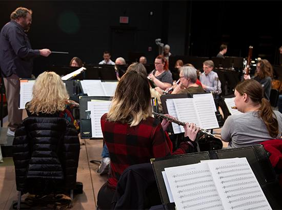 Band playing music with conductor leading