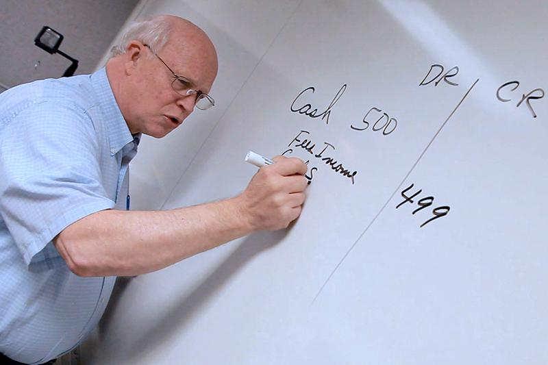 Image of accounting professor writing on white board.