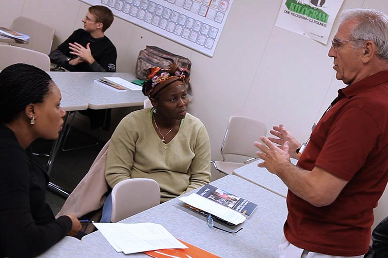 Image of instructor talking with student.