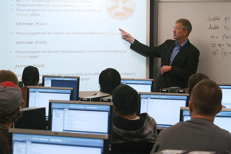 Math instructor pointing to screen and teaching students.