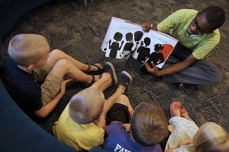 Image of person reading a book to kids.