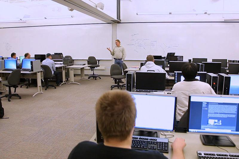 Image of instructor in front of whiteboard talking to a classroom of people.