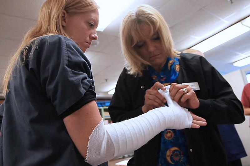 Instructor wrapping a student's arm in gauze.