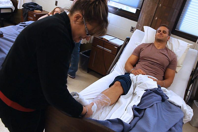 Image of nursing student wrapping a student's ankle.