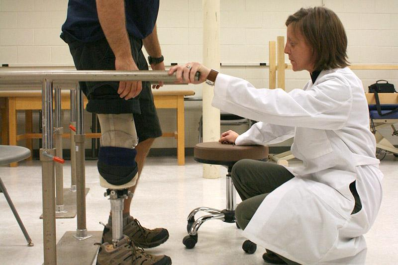 Image of student helping person with prosthetic leg.
