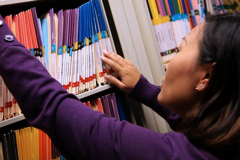 Image of woman looking through color-coded files.
