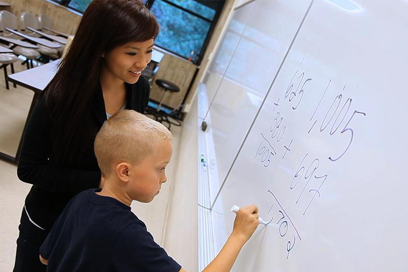 Image of woman helping kid write math on a whiteboard.