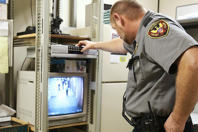 Image of public safety worker looking at a surveillance screen.