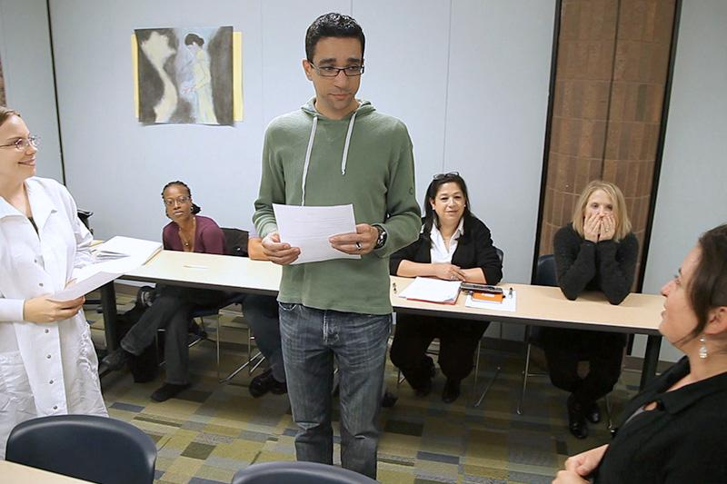 Image of student talking in front of class.