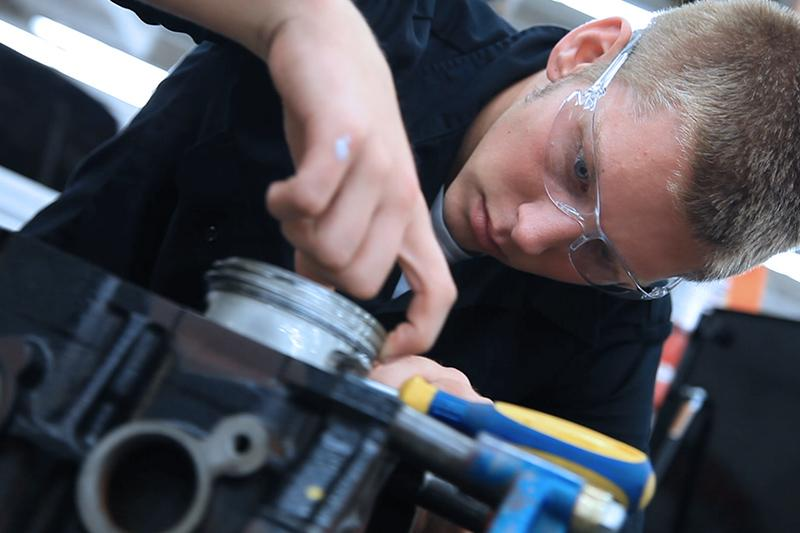 Image of Auto student with safety glasses on working on a machine.