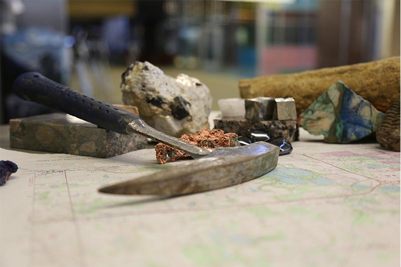 Image of pickaxe and earth science minerals and rocks.