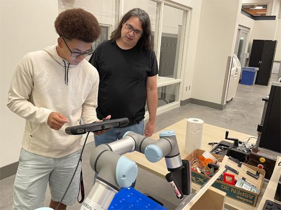 Two Additive and Digital Manufacturing students studying in the lab.