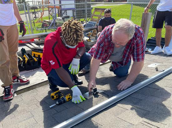 Faculty supporting students with the installation of Solar Panels on the roof on East Campus.