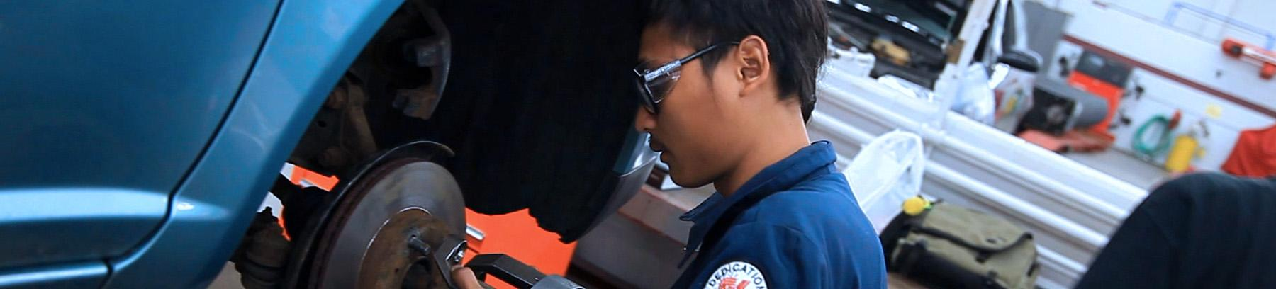 Image of auto student working on a car's breaks.