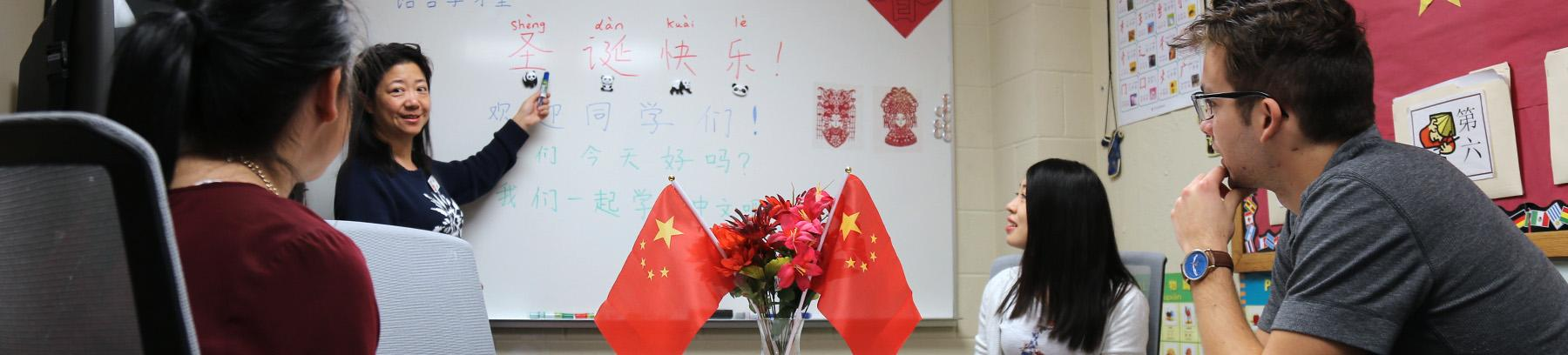 Chinese professor teaching students in front of whiteboard.