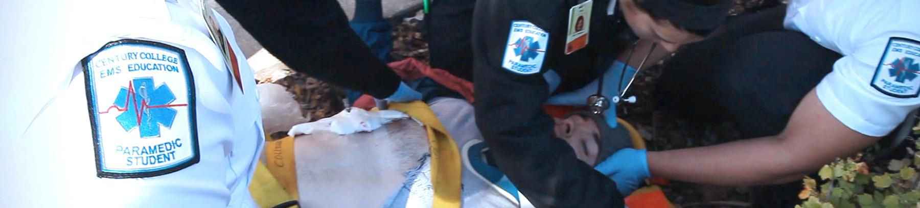 EMT students working on a student laying on a gurney.