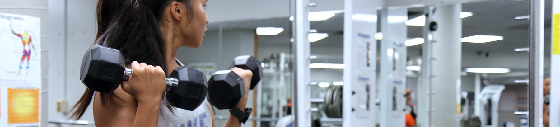 Image of female student lifting weights.
