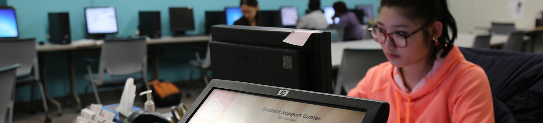 Image of student working on a computer in the student support center.